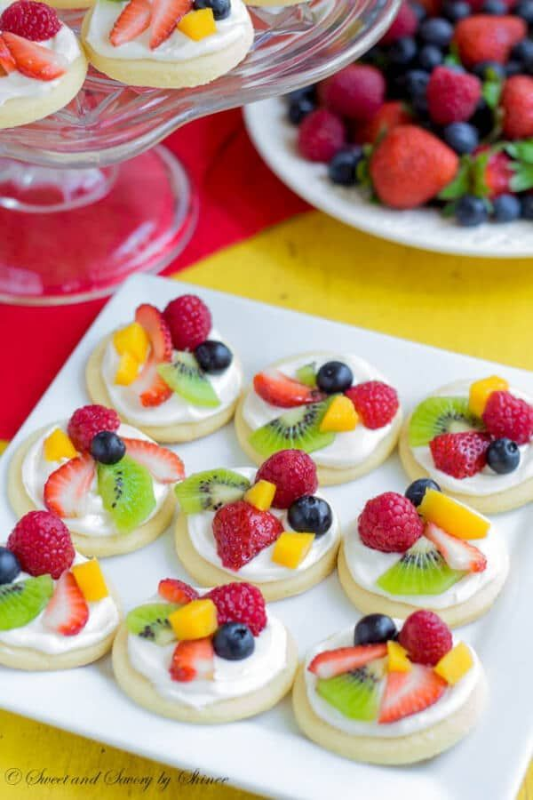 Summer classic in bite-size! These mini fruit pizzas are built on simple soft sugar cookies and topped with white chocolate cream cheese filling and colorful fresh fruits. #fruitpizza #minifruitpizza #partydessert #fruitdessert