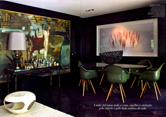 An abstract painting echoes the green chairs in a moody black dining room