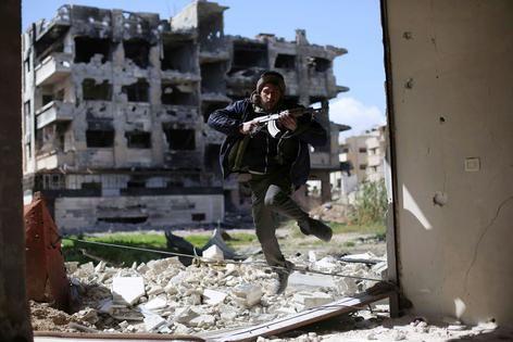 Een vechter van Jaish al-Islam zoekt dekking in de wijk Jobar, aan de oostelijke rand van de Syrische hoofdstad Damascus.