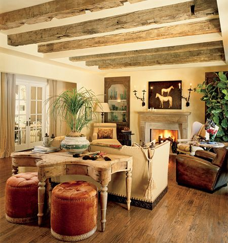 Warm n' inviting - love the table design with the 2 ottomans!