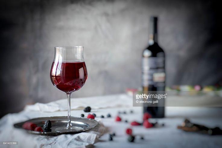 bicchiere di vino in primo biano su tavola con tovaglia ricamata, su sfondo bottiglia di vino, frutti di bosco sparpagliati sul tavolo