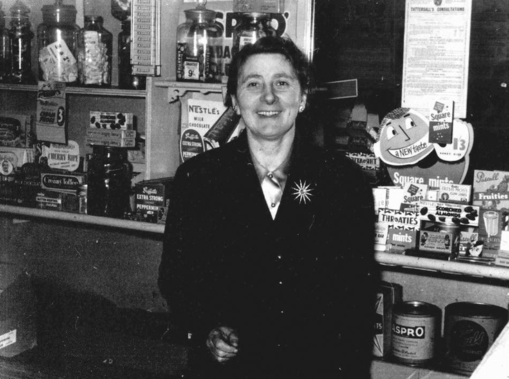 Black and white image of Elizabeth Cohen in her milk bar in North Carlton. The milk bar was called The Old Lolly Shop, it was opened and run by Elizabeth and Henry Cohen at 314 Rathdowne Street, Carlton North, Melbourne Victoria Australia from 1939 to 1975. Elizabeth and Henry Cohen both born in Australia, were descendants of Jewish immigrants from Europe.