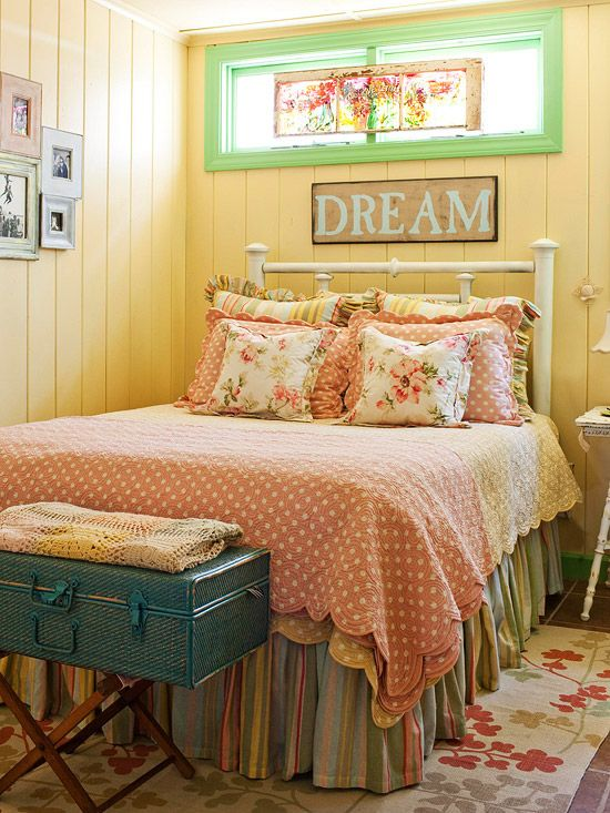 Sweet Color Scheme - Vanilla-yellow paneled walls bring light to a small bedroom in a snug lake cottage. Jade green frames the windows and mixes with rosy pink in a sweet confection of patterns on the rug and in the bed linens. A note of turquoise blue appears in the storage case at the end of the bed. The pastel palette enhances the cottage style and helps to harmonize the varied vintage furnishings.