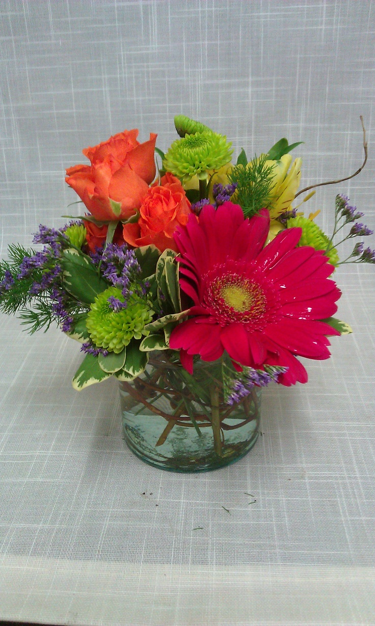 Bright citrus toned centerpiece includes gerbera daisies, yoko ono poms, spray roses and yellow alstroemeria.
