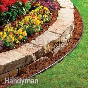 "This 4"" plastic edging filled with mulch against a stone border wall is a great way to reduce maintenance. The edging keeps grass roots from creeping into the stone wall, and the mulch provides a mowing track for the lawn mower wheels. You can mow right over the plastic border and cut the lawn edge cleanly. There's no need to trim the grass."