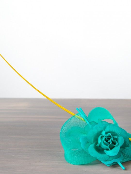 JOCKEY WHIP   Hat/Fascinator Spring Racing Carnival   FORD MILLINERY  $315  This filly is a favourite with the bookies, to match almost any silks. Jade/aqua sinamay teardrop base, with jade silk rose and stem right on the nose. The Jockey Whip – the yellow ostrich quill spine – takes the rails atop hand-sculpted jade crinolin. Correct weight.    Flower & feather combinations may differ depending on base colour selected. Hooded jacket by Alexi Freeman.