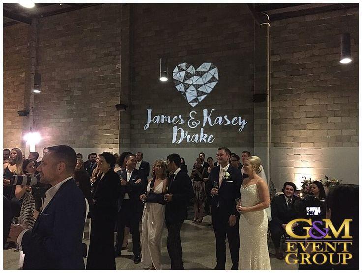 Kasey & James' wedding @ the Joinery West End - Wedding Cake | Wedding DJ + MC + Lighting | Custom Monogram | Warm White Uplighting #warehousewedding #uplighting #weddinglighting #custommonogram #weddingdj #weddingmc #gmeventgroup