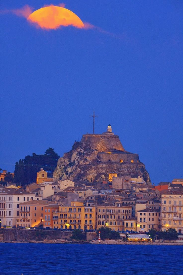 Cloudy full moon above Corfu town