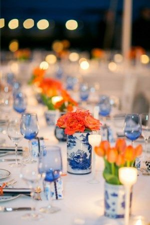 Beautiful tabletop with bright orange flowers and blue and white vases - Photo by Sarah Tew Photography
