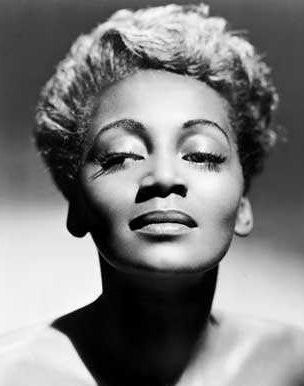 """Joyce Bryant was a blues and jazz singer in the 1940's and 50's. She was referred to as the Black Marilyn Monroe, and """"the Voice You'll Always Remember"""".  Remembered as a stunning performer with silvery blond hair offsetting a mahogany complexion, she rocketed to fame within the Black community and was regularly featured in magazines such as Jet and Ebony."""