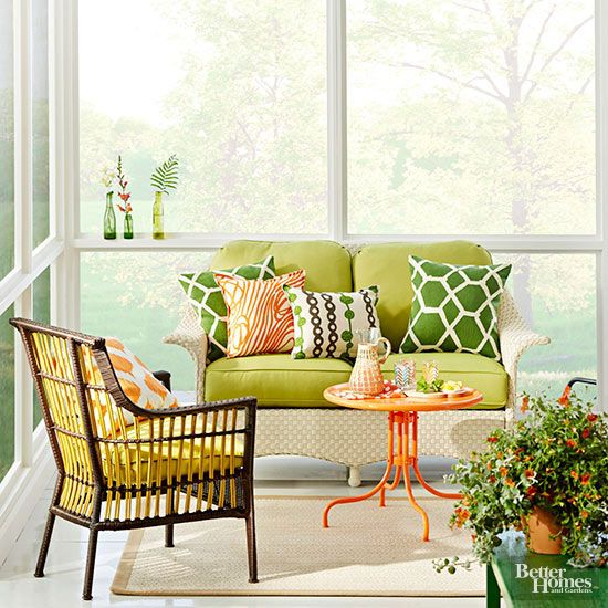 A petite seating group filled with exuberant colors inject this small porch with major personality. Yellow-greens pick up on the yellow in the wicker chair, while pops of orange complete the color trifecta. Secret to Pretty: Paying attention to scale. So your porch isn't massive. That's ok. Scaling down your furniture to suit your space will make it feel much more comfortable. Here, a love seat, rather than a full sofa, is sized right for the narrow porch.