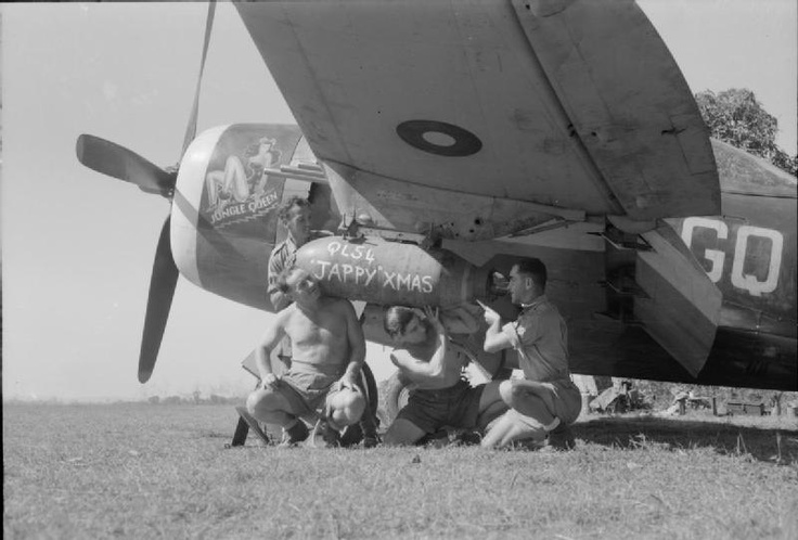 """Four ground crew of No. 134 Squadron RAF load a 500-lb GP bomb, - inscribed with a Christmas message for the enemy, - beneath the wing of """"Jungle Queen"""", a Republic Thunderbolt Mark II, at Ratnap, Burma. The airmen are (left to right): Leading Aircraftman James Rich of Glasgow, Aircraftman Cecil Cox of Ironbridge, Shropshire, Leading Aircraftman Richard Dunning and Aircraftman Edward Price of Tonypandy."""