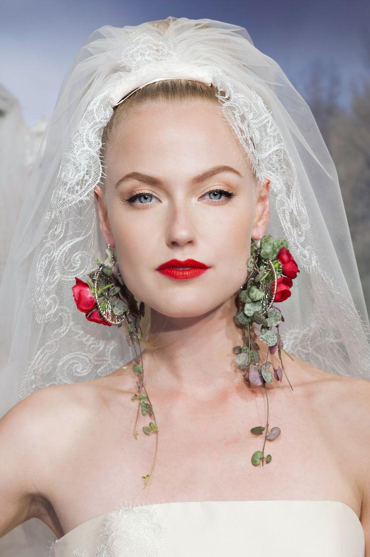 Capelli tirati all'indietro in uno chignon alto con il classico velo bianco e una decorazione di piccole rose rosse sugli orecchini. Aimee Montenapoleone, sfilata primavera/estate 2015.