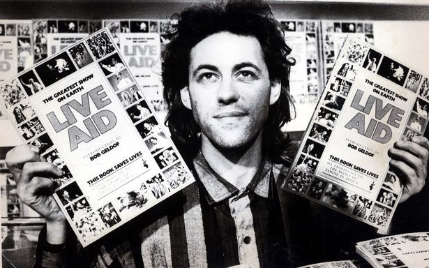 Bob Geldof Live Aid Concert Organiser And British Rock Musician Poses With The Official 'live Aid World-wide Concert Book' Of Photographs