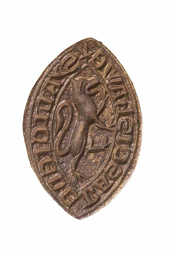 Seal matrix This form of seal die, a pointed oval known as 'vesica shaped', was used particularly by women and churchmen. This is a woman's seal, and bears her name around the edge: 'S' ALICIE DE BASCIShAWE' - 'seal of Alice of Bassishaw' - and a lion rampant in the centre.  Production Date: Early Medieval; 13th century