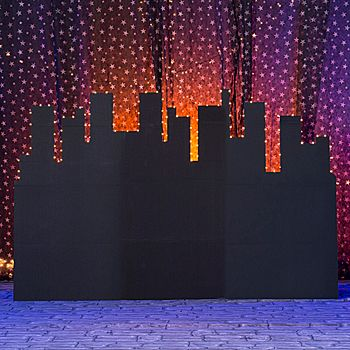 Complete your city scene with this Above the City Lights Skyline Background. The 8' high x 12' long Above the City Lights Backdrop Skyline is made of heavy black cardboard that stands on its own.