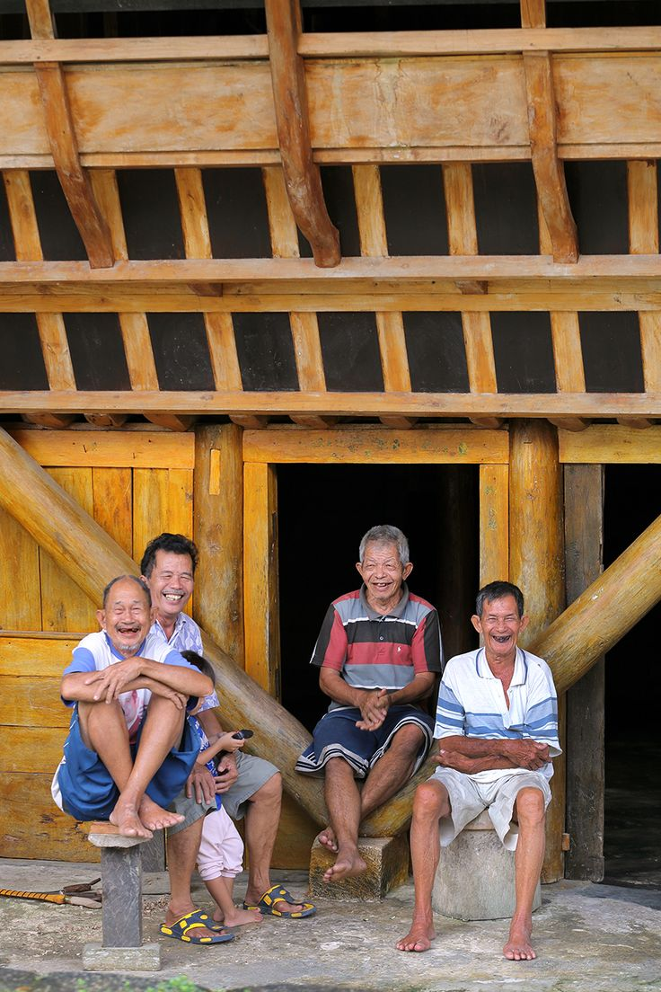 Friendly locals in front of a traditional house in Hilimondregeraya Village. Nias Island, Indonesia. Photo by Bjorn Svensson. www.visitniasisland.com