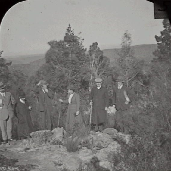 Title: Caley's Repulse Date & Location: 6 September 1912, Linden (NSW) Description: Black and white glass lantern slide. Title in ink on upper edge label. Pasted label upper right: F.W. 5. Notes: Group portrait of members of Australian Historical Society, taken on occasion of 'discovery' of 'cairn' of stones at Linden, known as Caley's Repulse. From negative in Mitchell Library Frank Walker Collection ON 150, Item 977A.