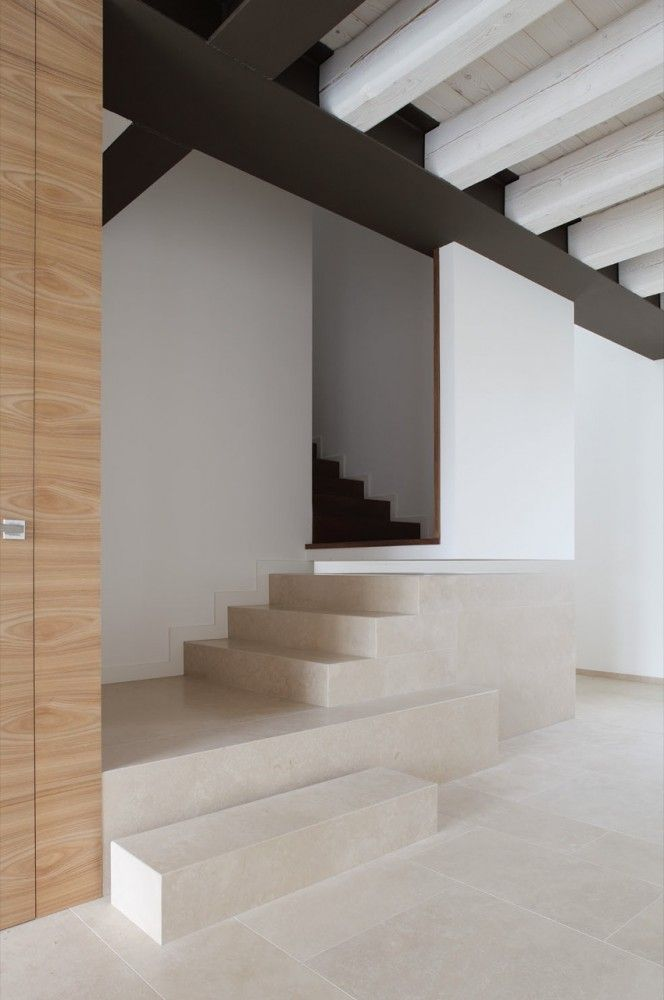Farmhouse renovation by EXiT architetti associati. I like the contrasting shape and sizes of the various stairs. They create a connection with the exposed beam ceiling, and widen/open out the space. The lack of a railing adds to the openness.