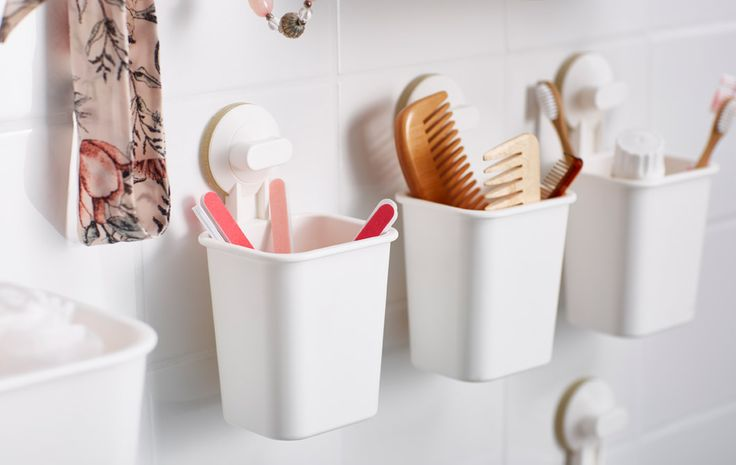 Small plastic baskets are attached to the bathroom wall with suction cups and hold toiletries and accessories.