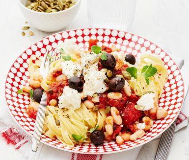 En medelhavsinspirerad pasta som kommer att sprida väldoft i hela köket. Matiga, lena cannellinibönor får puttra i den mustiga tomatsåsen med kapris, svarta oliver, het röd peppar och oregano. Servera såsen med nykokt tagliatelle, garnera med mozzarella och krispiga pumpafrön.