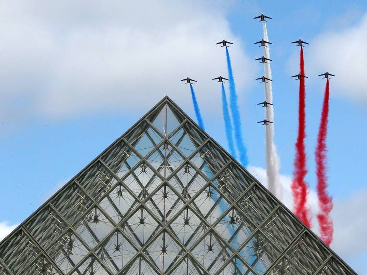 14 July 2015. Alphajets from the French Air Force Patrouille de France in the formation of a Croix de Lorraine cross and releasing trails of red, white and blue smoke, colors of French national flag, fly over the Pyramid of the Louvre Museum during the traditional Bastille day military parade in Paris, France.
