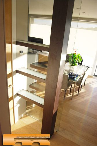 columna forrada y estantes con cristal y iluminación interior. Proyecto de fusteriamanel.com