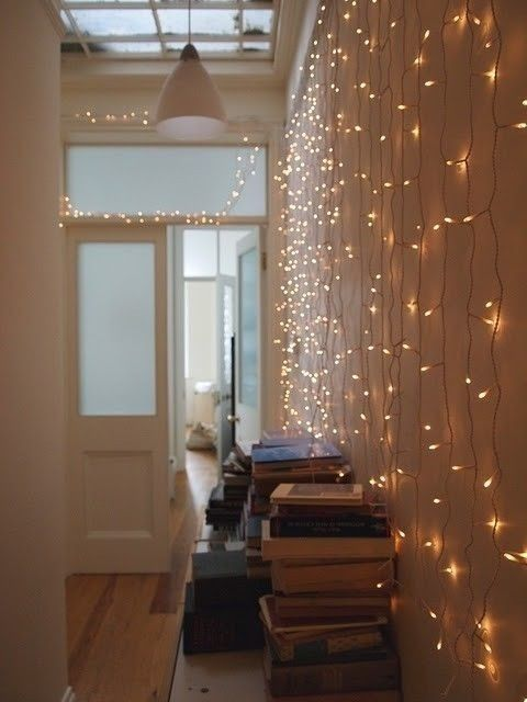 twinkling Christmas lights on white wall with old books. perfect.