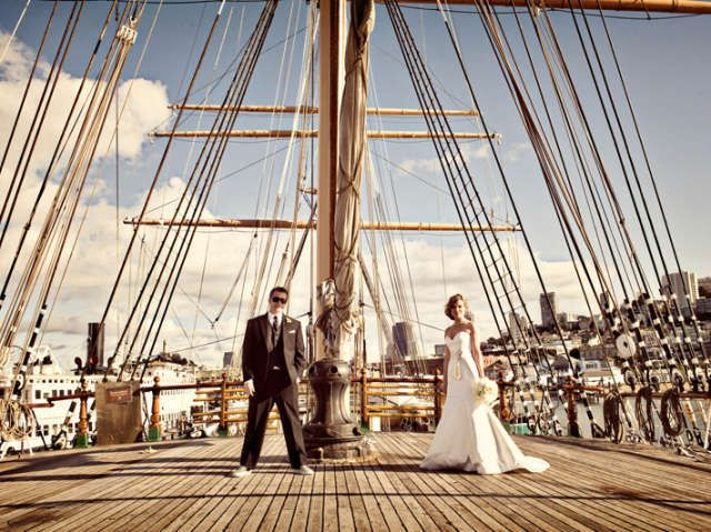 A San Francisco bride and groom pose on the deck of a large ship.