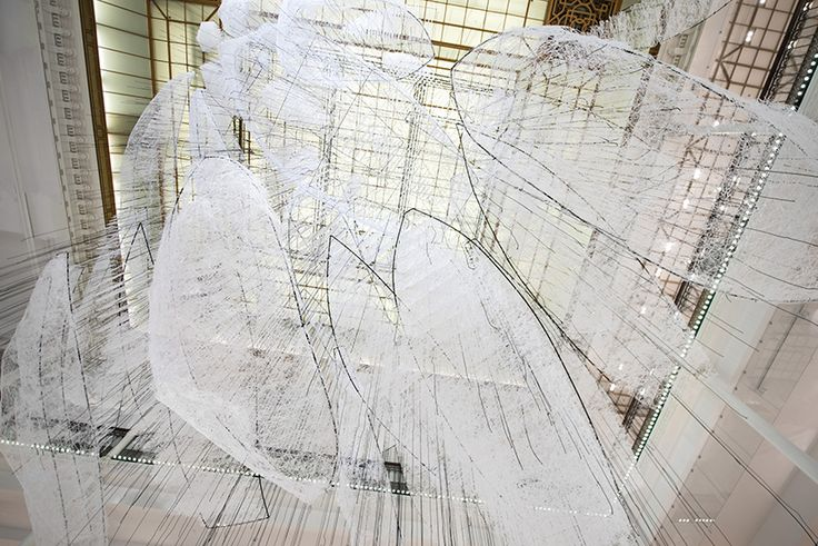 inside the historic le bon marché department store in paris, japanese artist chiharu shiota has suspended 150 sculptural boats from the ceiling, figuratively 'sailing' across the space. drawn from typologies found across a range of cultures and communities, the hollowed out metal hulls — seemingly etched with a pencil — hang from the store's central glass roof, surrounding visitors in an all-white abyss.