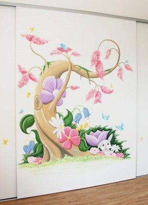 Fantasieboom in Disney stijl voor in een meisjeskamer met veel bloemen, vogels en vlinders en natuurlijk roze! De muurschildering is op schuifdeuren van een kledingkast gemaakt.