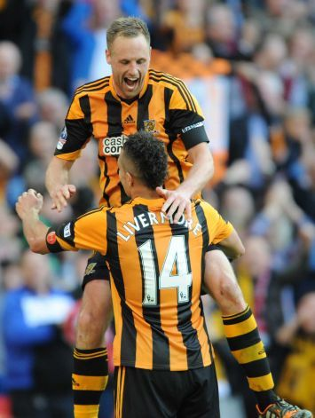 Hull City's David Meyler, top, celebrates with teammate Jake Livermore after scoring against Sheffield United during their FA Cup semifinal soccer match between Hull City and Sheffield United at Wembley Stadium, Sunday, April 13, 2014.