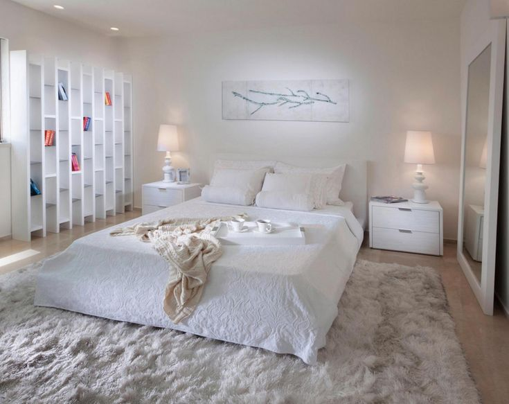 Stylish white bedroom interior with a big modern floor bedding on a furry carpet decortaed by lovely veiled lamps and large floor mirror