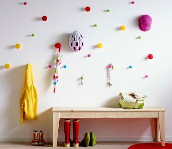 Färgglada knoppar i olika höjder på en hallvägg som det hänger barnkläder och accessoarer från, samt en bänk med skor under.