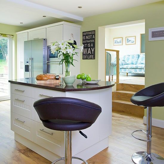 Kitchen Island in modern design. White kitchen units with black worktops.