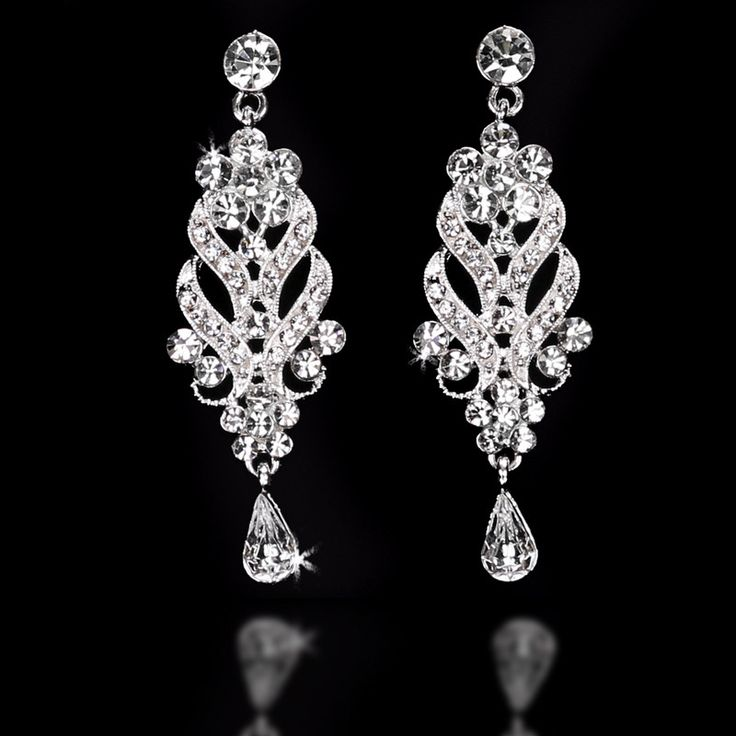 These elegant chandelier bridal earrings are designed with flowers, scrolls and sparkling teardrop jewels in silver. They are about 2.5 inches long and .5 inches wide.