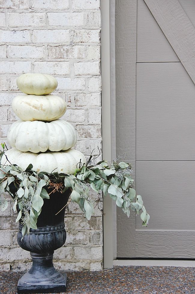 concrete urn painted black with still life of squash and dried greens. Rustic and Lovely against the painted brick. The Tour of the House That Photographed Itself