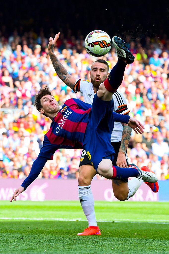 Lionel Messi of FC Barcelona performs an overhead kick under a challenge by Nicolas Otamendi of Valencia CF during the La Liga match between FC Barcelona and Valencia CF at Camp Nou on April 18, 2015 in Barcelona, Catalonia.