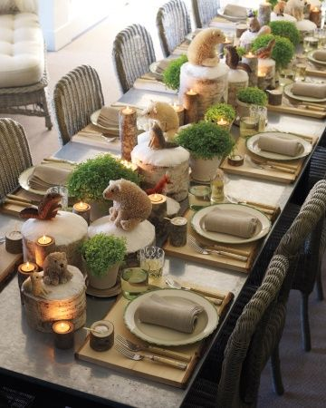 """Rustic, woodsy decorations naturally say Christmas. This table is set with wood-plank place mats, branch candleholders, and """"snowcapped"""" birch stumps. The Buri animals and the pots of selaginella, or spikemoss, evoke a dreamy forest floor."""