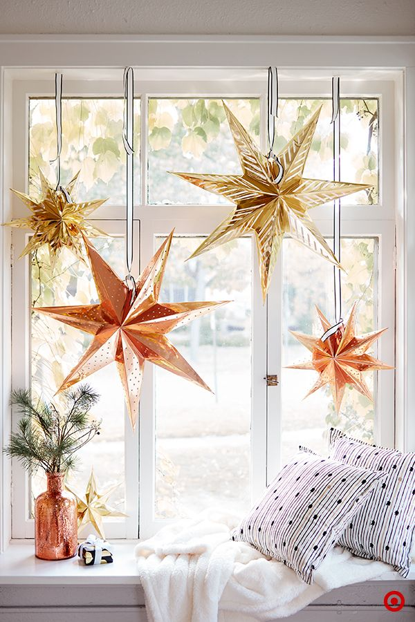 It's easy to add holiday glam, even if your spaceis on the neutral side. Metallic paper star lanternsin a mix of sizes will feel just as celebratoryhanging in a window in the living room as they will above a holidaydinner table. (We kept the minimal feel going bypairing the stars with black-and-white stripedribbon from our Sugar Paper for Target collection.) And they work for dayor night—let the sun shine through or light themup with a simple light cord.