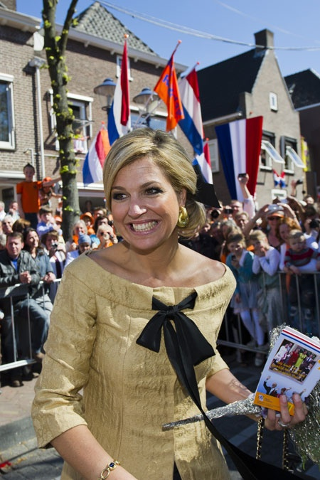 Prinses Máxima in een goudkleurige jurk met opvallende, zwarte strik van de Belgische ontwerper Edouard Vermeulen (Natan).