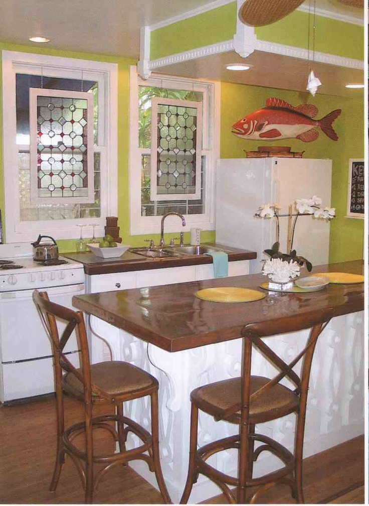 """The kitchen area offers an """"Eat-At"""" bar.  Antique stain glass hangs in the windows"""