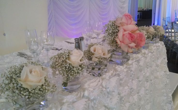 Baby breath and roses line up on a head table