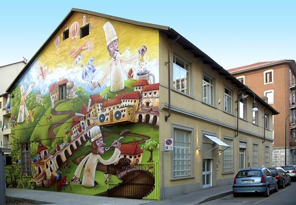 Guido Gobino is one of the most famous chocolate manufacturers in Italy, distinguishing his recipes with exotic and unusual ingredients. This mural was painted during the annual Cioccolatò event in Torino. The 13 x 10 meter blind façade of the Gobino laboratory in via Cagliari 15/B was entirely covered by an illustration representing a huge outdoor chocolate factory in a natural setting where Torino architectures can be recognized.