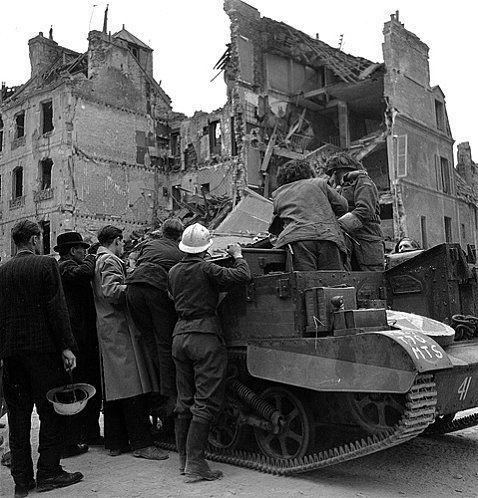 Des civils et des membres de la Défense Passive ( casques Adrian peints en blanc ) se sont regroupés autour d'un Bren carrier canadien, ils attendent probablement du ravitaillement. Les habitations de l'arrière-plan sont totalement détruites.