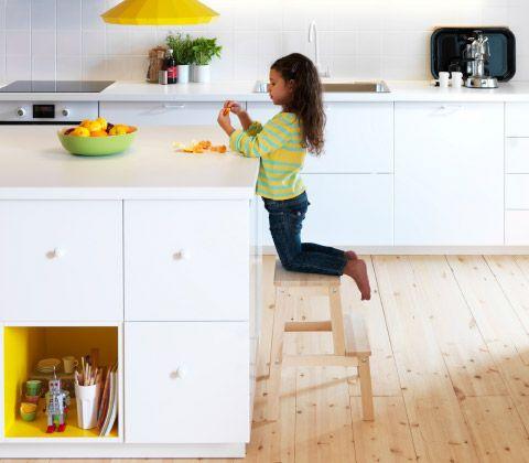 un nio pelando una naranja de rodillas sobre un taburete en una moderna cocina blanca