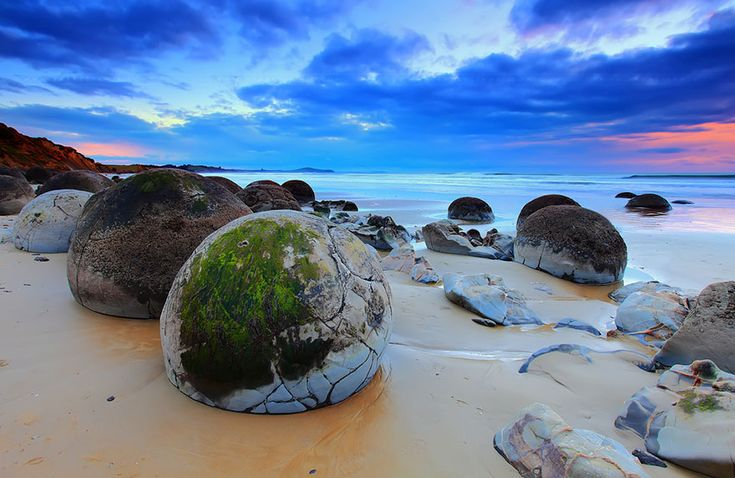The boulders on this New Zealand beach are concretions – balls of sedimentary rock harder than the sedimentary earth that formed around them, which has long since washed away. These boulders get uncovered and smoothed by pounding waves.