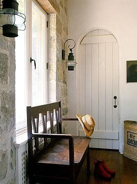 Rustic beautiful entryway foyer. Love the bench and stone wall, wood floor, white door!