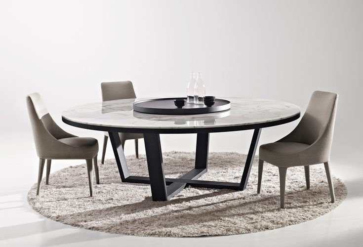 The distinguishing feature of the Xilos table collection, available in a square version (178x178 cm) and three round sizes, is its cross-shaped  frame in grey oak, brushed light oak, black oak or smoked oak. The round version is also available with a top in white Calacatta marble or Emperador marble and can be paired with a  swivel tray in two sizes (∅ 70 cm and ∅ 110 cm) and six finishes (the same types of wood as the frame or with a top in white Calacatta marble or Emperador marble).