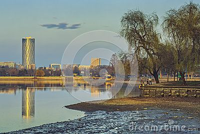 Bucharest, Romania - March 09, 2013: Idyllic scenery in Herastrau park with buildings reflections on the lake surface on a spring serene morning.